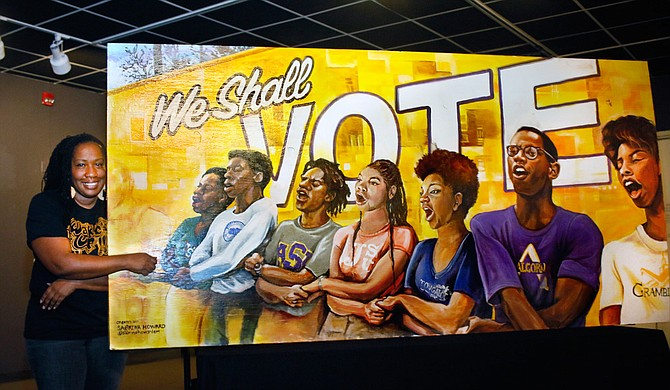 "Sabrina Howard poses with her ""We Shall…"" mural, which is one of six murals included in the local ""#ArtofVoting"" series. Photo courtesy Sabrina Howard"