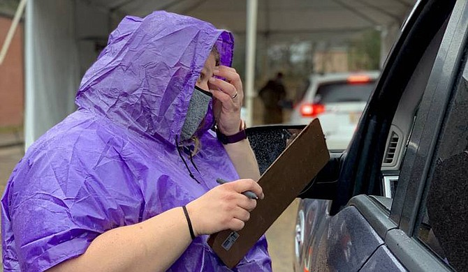 A Madison drive-through worker helps guide people through the vaccination process. The site is one of 19 drive-through clinics in the state. Photo courtesy MSDH