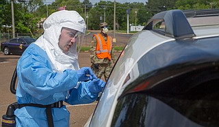 """U.S. Air Force Senior Airman Jacob Cranston explains testing procedures to a patient at a mobile testing site in Natchez. """"Vaccination Day"""" is one of several planned events to promote vaccinations among Jackson's vulnerable population who may have difficulty otherwise obtaining them from other sites. U.S. National Guard photo by Spc. Jovi Prevot"""
