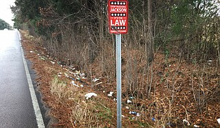The City of Jackson put a sign on West Highland Drive saying those who throw trash beside the street will a $1,000 fine. But it seems not to be working. Photo by Kayode Crown