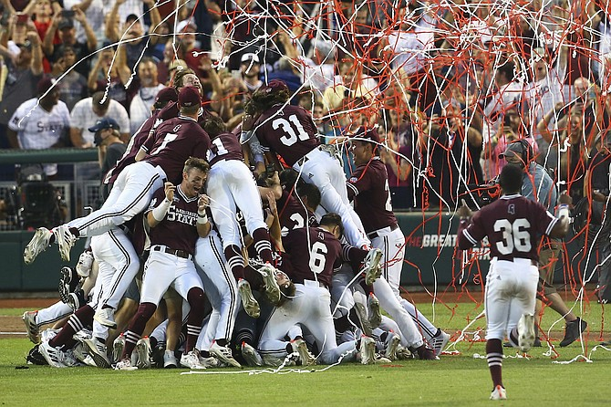 """Mississippi State University baseball players jump on the """"dawg pile"""" after their historic win in the College World Series."""