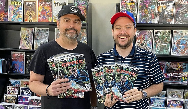 """Music and graphic artist Jason Turner (left) poses with Travis Ryder, co-owner of Van's Comics, Cards and Games in Ridgeland, Miss., which offers issue #0 of """"The Ripper Gene,"""" a comic series based on a mystery novel of the same name. Photo courtesy Jason Turner"""