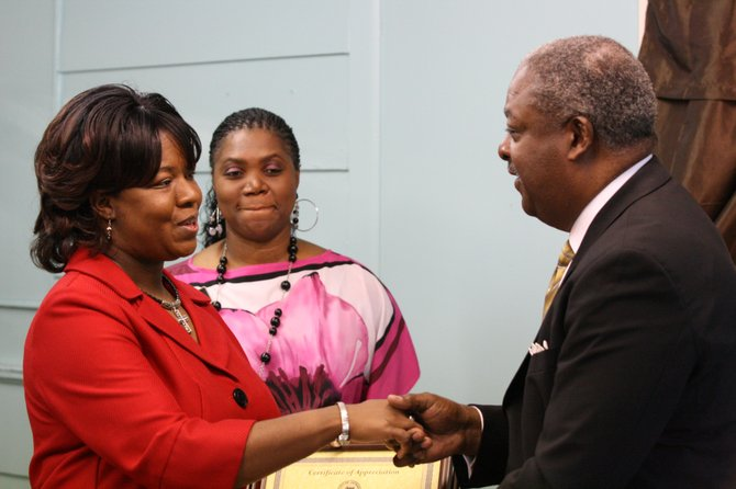 Mayor Harvey Johnson Jr., right, presents Shuntel's Boutique owner Yalonda Gladney, left, with a certificate of appreciation at the store's grand opening today.