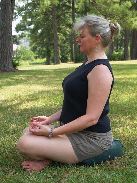 Debi Lewis of JoyFlow Yoga demonstrates good meditation posture using a zafu cushion.
