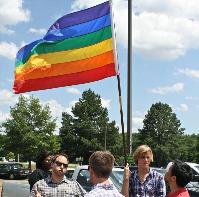 Bob Gilchrist holds a rainbow flag as gay-rights protestors organize at the Ag Museum Tuesday afternoon.