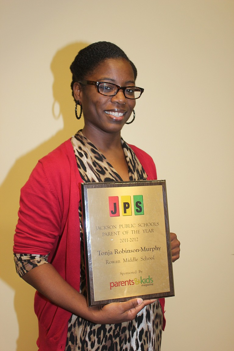 Tonja Robinson-Murphy poses with her plaque for Jackson Public Schools Parent of the Year 2011-2012.