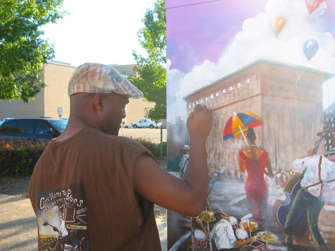 Tony Davenport puts the finishing touches on his painting on a traffic signal box in downtown Jackson.