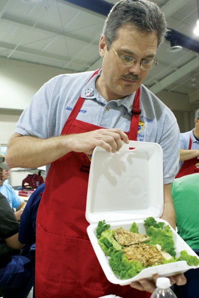 Table captain John Lacourrége displays a plate of barbecue chicken for judging at the Kansas City Barbeque Society judges class at St. Francis of Assisi in Madison.
