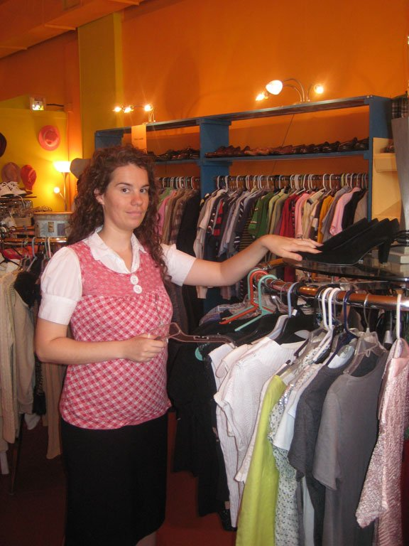 Shopkeeper Kristin Tubb restocks the clothing racks with new items in The Orange Peel.