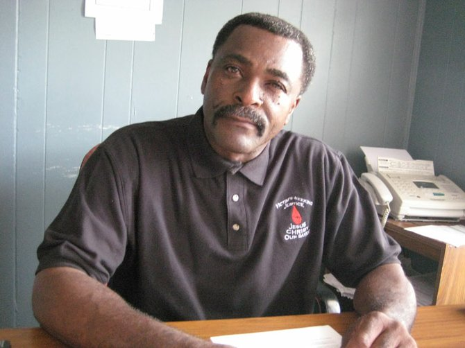 Larry Nelson Sr., at his desk at Hometown Auto Sales on Robinson Road, is offering a $10,000 reward to find who killed his son, Larry Nelson Jr.