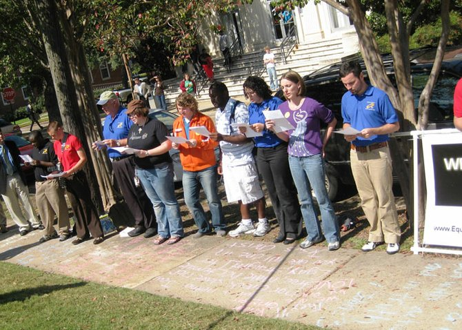 SoulForce riders and Mississippi College students recite an anonymous letter from an MC student on the sidewalk in front of Aven Hall on College Street.